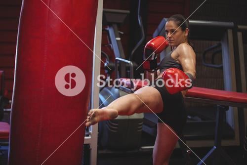 Female boxer practicing kickboxing