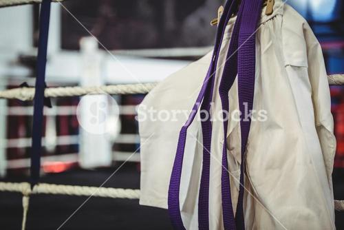 Karate uniform and purple belt in boxing ring