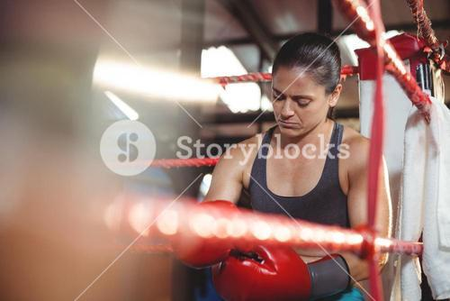 Tired female boxer sitting in the ring