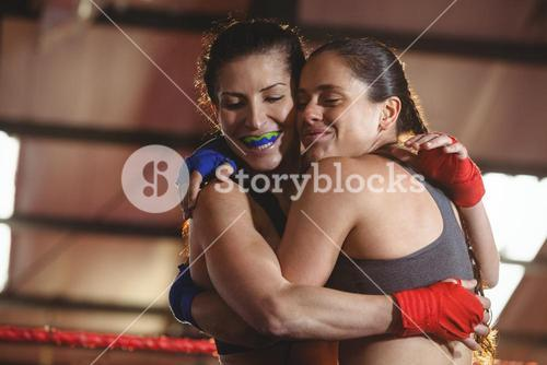 Two female boxers hugging each other in the ring