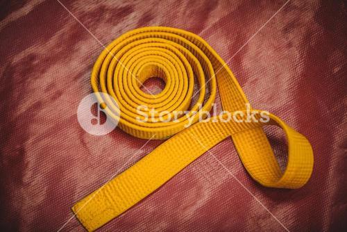 Karate yellow belt on red background
