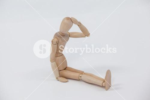 Tensed wooden figurine sitting with hand on head