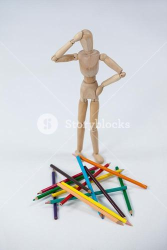 Confused wooden figurine standing near a heap of color pencils