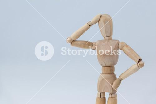 Confused wooden figurine standing with hand on head