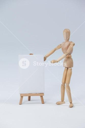 Wooden figurine standing next to white board and giving a presentation