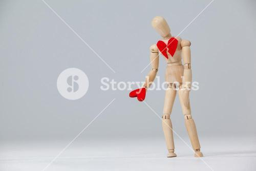 Wooden figurine with a broken heart and holding a red heart