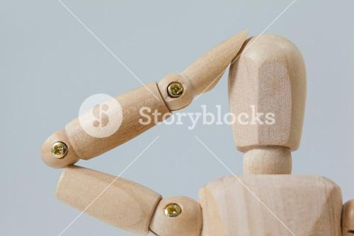 Confused wooden figurine with hand on head