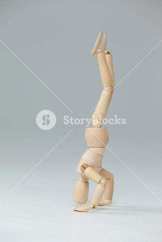 Wooden figurine performing a headstand
