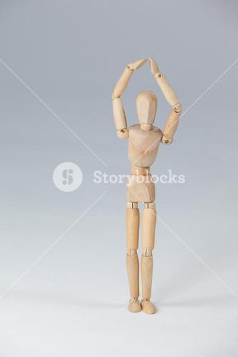 Wooden figurine standing with hands raised
