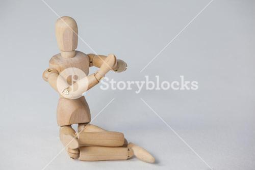 Wooden figurine performing yoga on floor
