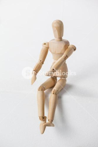 Wooden figurine sitting with his hands forward