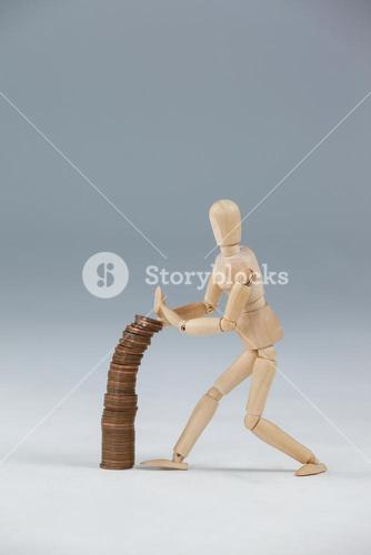 Wooden figurine preventing stack of coins from falling
