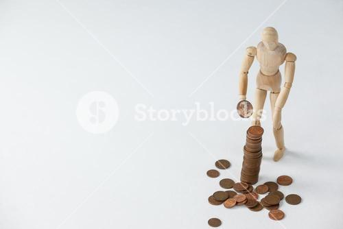 Wooden figurine standing and making stack of coins