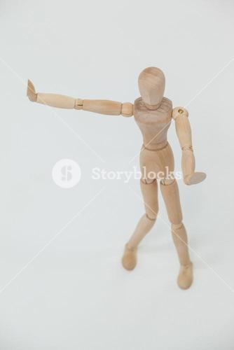 Wooden figurine standing and showing hand stop sign