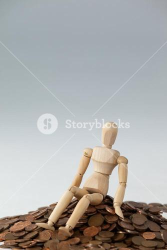 Wooden figurine sitting on heap of coins