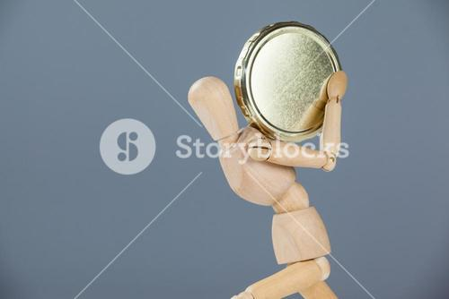 Wooden figurine holding a gold coin