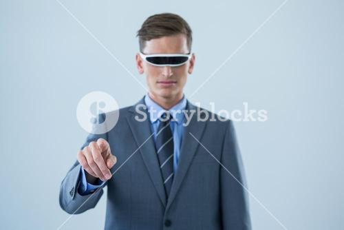 Businessman pointing his finger while using virtual reality glasses
