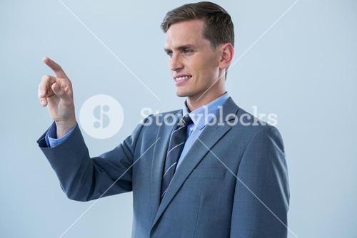 Smiling businessman touching an invisible screen