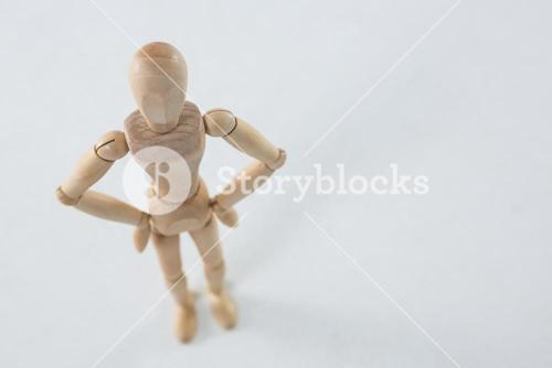 Wooden figurine standing with hands on hip