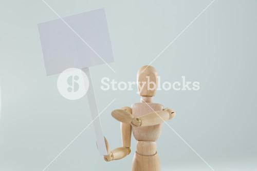Wooden figurine holding blank sign board