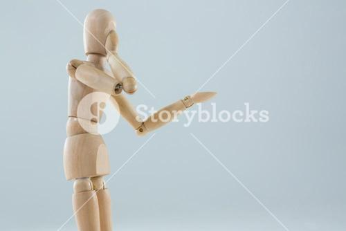 Wooden figurine applying makeup