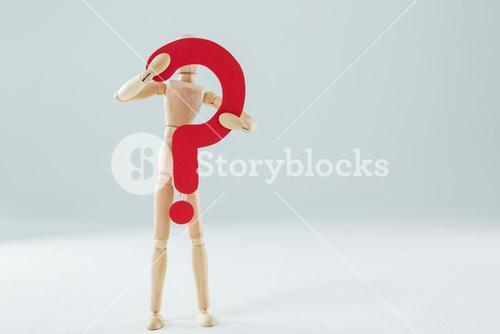 Wooden figurine holding a question mark sign