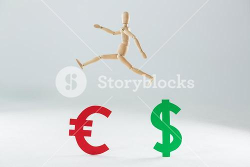 Wooden figurine jumping over dollar and euro symbol