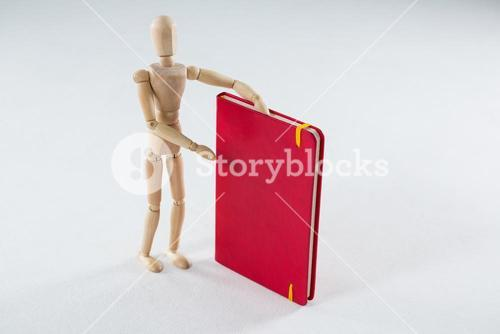 Wooden figurine showing a book