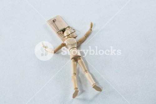 Wooden figurine caught in the mouse trap