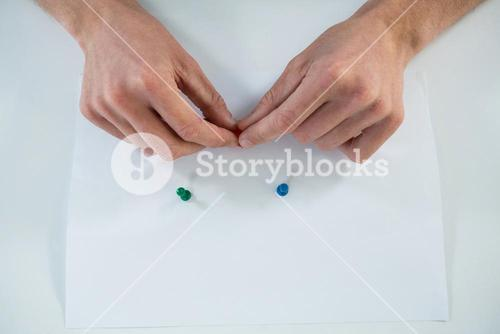 Man attaching push pin on paper