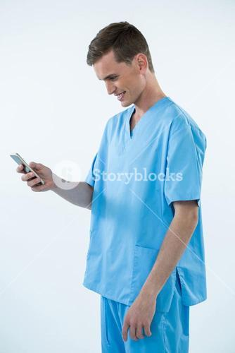 Smiling male nurse using mobile phone