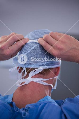 Surgeon tying surgical mask in operation room