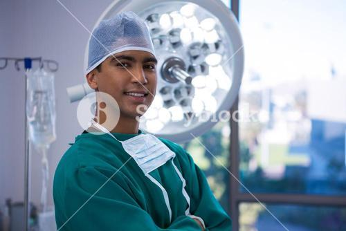 Portrait of surgeon standing with arms crossed in operation room