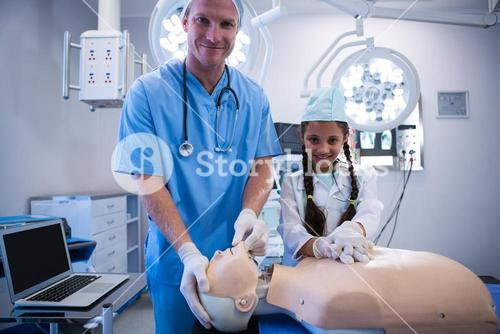 Portrait of doctor and girl examining a dummy
