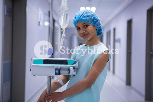 Portrait of smiling girl with iv drip standing in corridor