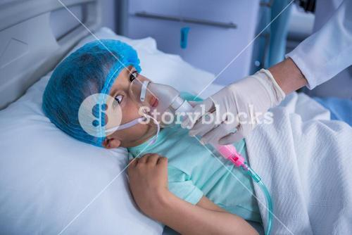Doctor placing an oxygen mask on patient in ward