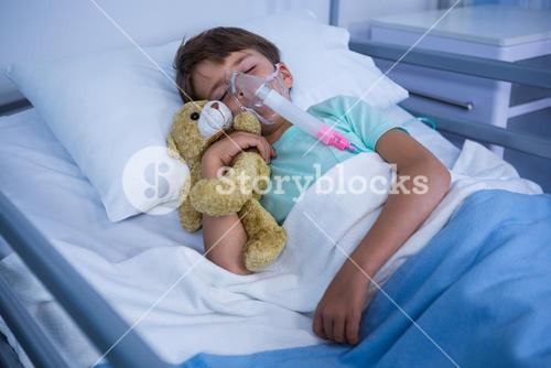 Patient with oxygen mask relaxing on bed in ward