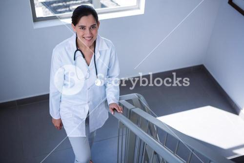 Portrait of doctor walking on staircase