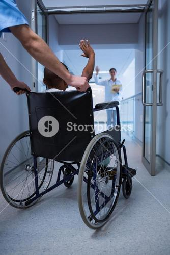 Boy sitting on wheelchair and waving hand to doctor in corridor