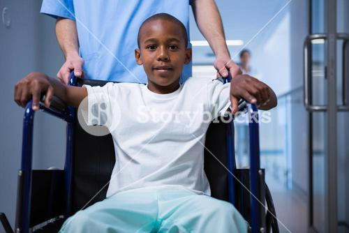 Portrait of boy sitting on wheelchair in corridor