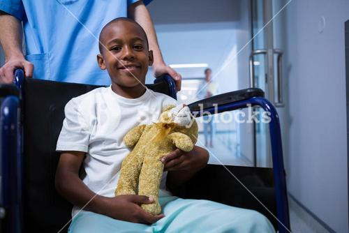 Portrait of boy sitting on wheelchair and holding teddy bear in corridor