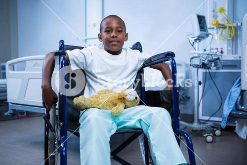 Portrait of boy sitting on wheelchair with teddy bear in ward