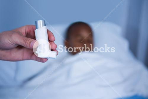 Hand of nurse holding asthma pump in ward