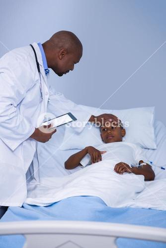 Male doctor checking patient fever during visit in ward
