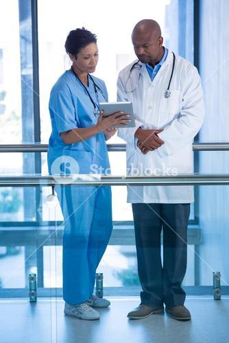 Male doctor and nurse using digital tablet in corridor