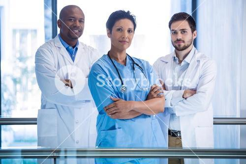 Portrait of male doctors and nurse standing in corridor