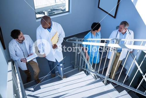 Doctors interacting with each other while climbing stairs