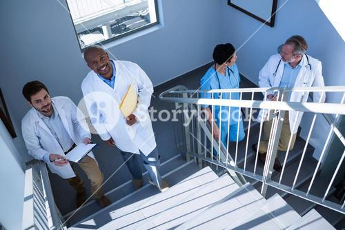 Portrait of doctors interacting with each other while climbing stairs