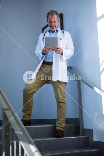 Doctor using digital tablet on staircase