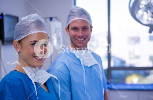 Portrait of male and female nurse smiling in operation theater